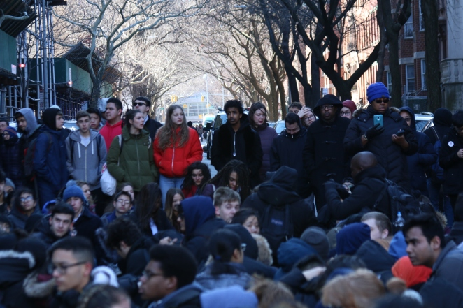 Students sit and kneel in the street in protest.